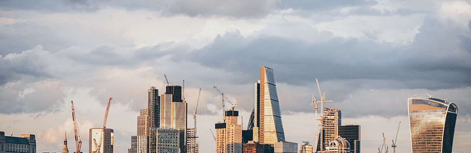 A view of the city of London, showing construction work and cranes in the background