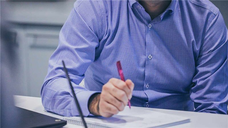 Man in Blue Shirt Writing Notes - Mace Group