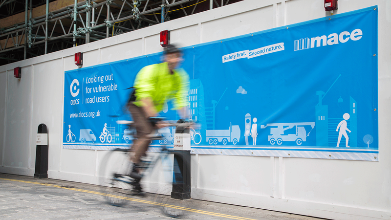 Cyclists Passing by a Mace Banner - Mace Group