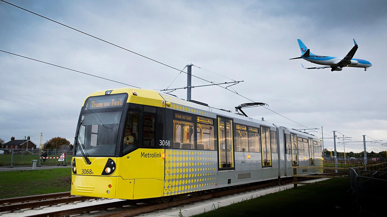Blue Tui Plane Flying Over a Yellow Tram - Mace Group
