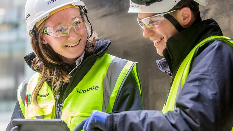 Female Constructor Smiling at Male Coworker - Mace Group
