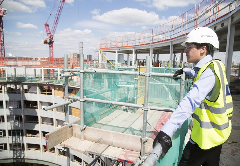 man looking over a balcony on a construction site