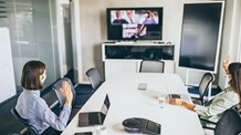 Two female employees in a meeting room virtually collaborating - Mace