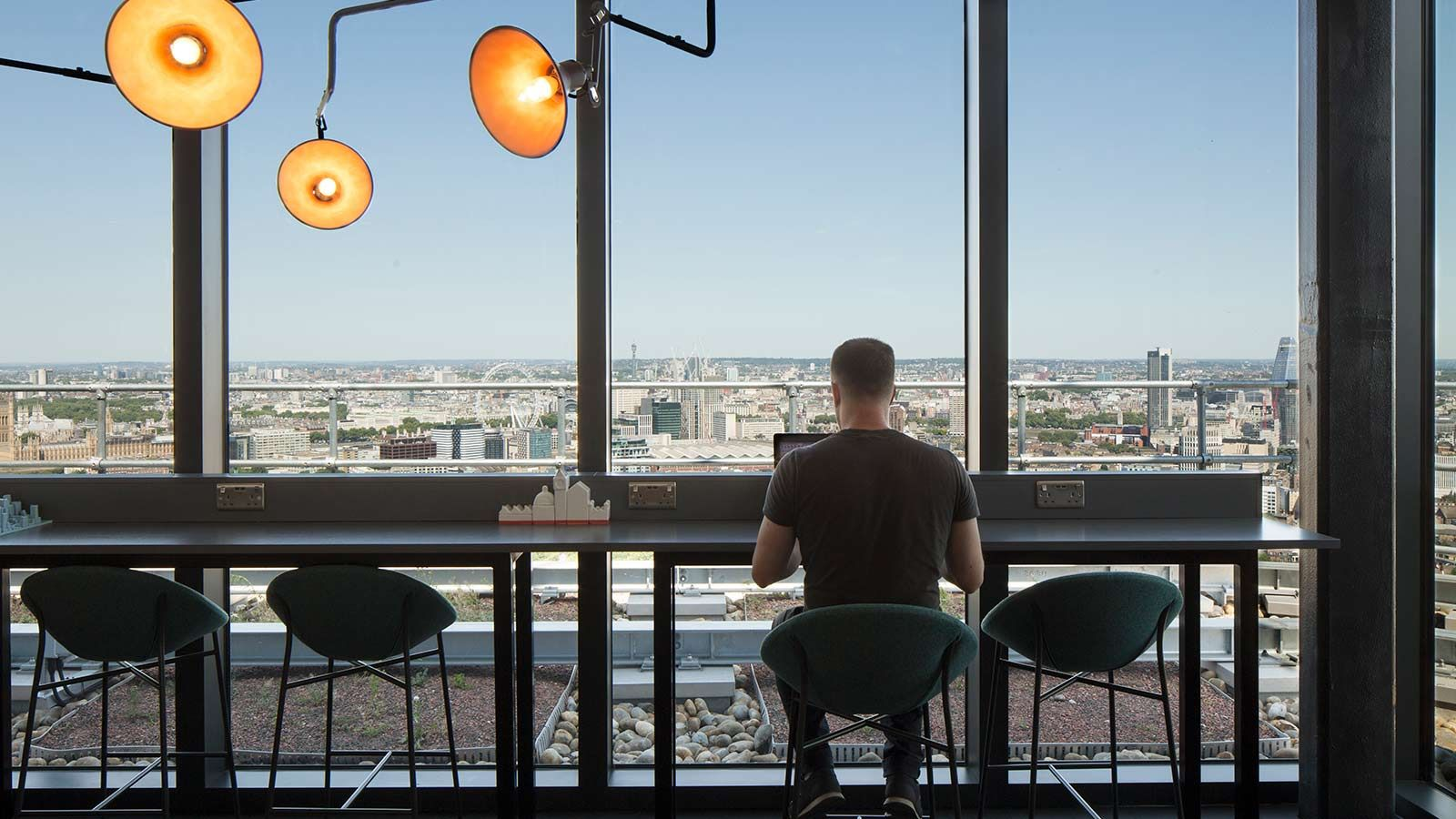 Resident working on laptop in Sky lounge - Mace Group