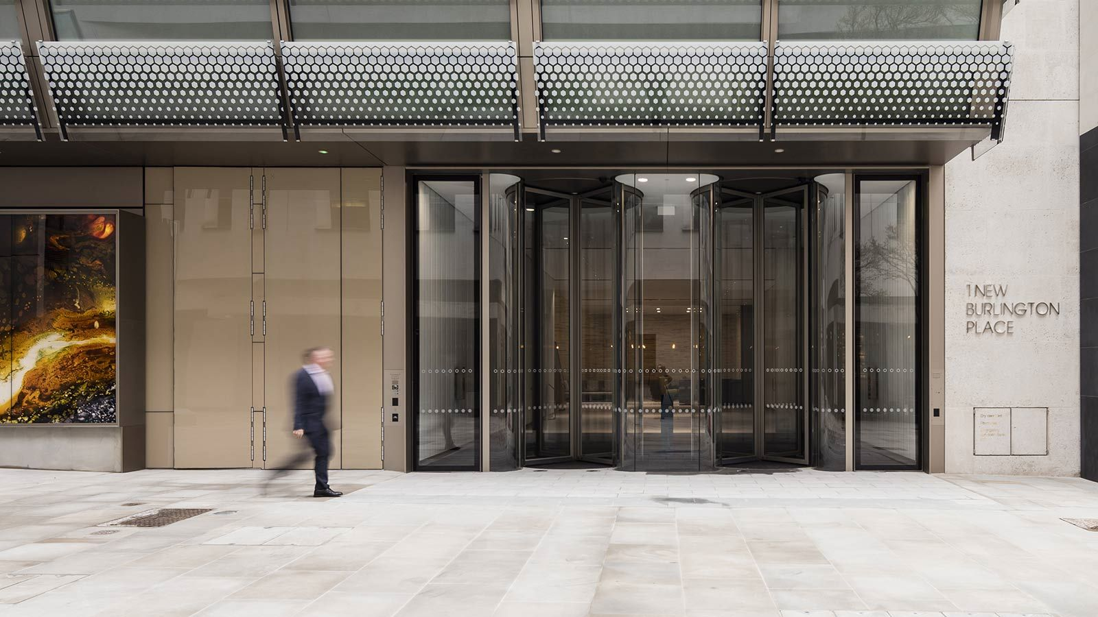 Person Walking in Front of W5 – New Burlington Place Building - Mace Group